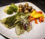 Branzino in crosta di erbe con patate novelle e verdure
